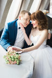 Vertical photo of the bride stroking the cheek of the smiling groom while sitting in the restaurant. stock photo