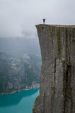 Vertical photo 0f tourist standing at Prekestolen rock's edge. Stock Photography