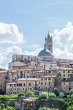 View on the famous cathedral in the town of Siena behind other historic buildings. Vertical photo of famous cathedral from white and black marble in the town of Royalty Free Stock Images