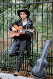 Fence in park. Vertical photo guitar player near metal fence in the park stock image