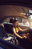 Vertical photo of happy rich young girl driving car with bag ful Royalty Free Stock Photography