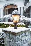 Lamp Ligtht in front of Home with Snow on Top Stock Image