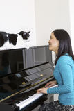 Mature woman and her cat looking at each other during piano sess. Vertical photo of mature woman with her family cat on top of piano looking at each other while Royalty Free Stock Photos