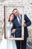 Vertical photo of newlywed couple looking through portrait frame Royalty Free Stock Photos
