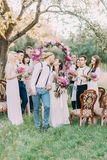 The vertical photo of the nice ceremony in the sunny field. The lovely newlyweds are kissing at the background of their. Guests and the wedding peonies arch stock images