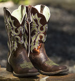 Fancy Western Boots. Vertical photo of a Pair of Brown Fancy Western Boots on rock with blurred grey background Stock Image