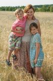 Gravid mother with children in rye field in a sunny windy day. The vertical photo of a pregnant mother hugging her two kids in rye field in a sunny windy day Royalty Free Stock Photo