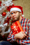 Vertical photo of sed lonely nerd with christmas gift Royalty Free Stock Images
