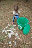 Child in blue latex gloves, throwing plastic bag into recycling bin. Land and rubbish on the background. Stock Image
