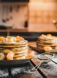 Vertical photo - stack of golden pancakes with bananas and oranges on wooden board covered with caster sugar. Heap of american. Pancakes with maple syrup with stock photography