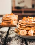 Vertical photo - stack of golden pancakes with bananas and oranges on wooden board covered with caster sugar. Heap of american. Pancakes with maple syrup in stock images