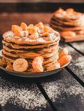 Vertical photo - stack of golden pancakes with bananas and oranges on wooden board covered with caster sugar. Heap of american. Pancakes with maple syrup in stock photo
