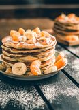 Vertical photo - stack of golden pancakes with bananas and oranges on wooden board covered with caster sugar. Heap of american. Pancakes with maple syrup in royalty free stock photo
