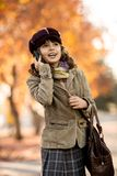 Happy girl outdoor. Vertical photo, stylish beautiful little girl hold mobile phone and gladness talk royalty free stock photos