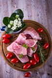 Few long slices of pork meet on chopping board with tomatoes. Vertical photo with top view on few slices of pork meat with fat on the edge. The green parsley Royalty Free Stock Photography