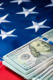 Vertical photo view of a stack of money lying on the flag of the United States of America. Close-up royalty free stock images