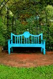 Vertical photo of a vivid blue colored wooden bench on terracotta brick pathway royalty free stock photos