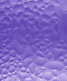Vertical photo of water drops texture macro shot on bright purple glass with selective focus Royalty Free Stock Photo