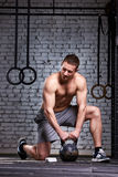 Vertical photo of young athletic man while holding kettlebell on the gym floor against brick wall. Stock Photos