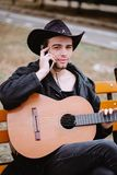 Phone and music. Vertical photo young man in park who speak phone with guitar in hands royalty free stock images