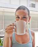 Young woman enjoying and drinking a cup of coffee after ride a bicycle Stock Photo