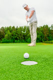 Vertical picture man playing golf. On a green field Stock Photos