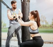 Vertical picture of a slim girl doing squats. She is holding the loops to keep balance. Young man is standing besides. Vertical picture of a slim girl doing Stock Photography
