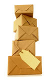 Vertical pile of brown paper parcels or packages, blank manila label, isolated on white background Stock Image