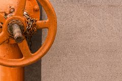 Vertical pipe painted bright orange paint with big valve with chain mounted on the base closeup copy space stock images