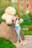 Vertical portrait of a beautiful girl with a huge bear. In the park Stock Photos