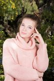 Vertical portrait of a beautiful young woman in a pink sweater in a lush garden. Knitted sweater. Fresh clean skin. A gentle smile Royalty Free Stock Photography