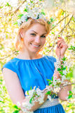 Vertical portrait of blond in cherry blossoms Royalty Free Stock Image