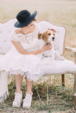 The vertical portrait of the bride petting the cute fluffy dog while sitting on the white old-fashioned sofa in the Stock Photo