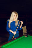 Vertical portrait of a charming blonde rubbed cue chalk royalty free stock image