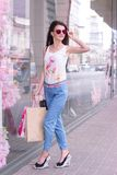 Vertical portrait of charming young lady in glasses with shopping Stock Images