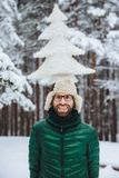 Vertical portrait of cheerful bearded man has fun alone in winter forest, keeps artificial fir tree, poses outdoors, admires frost stock photography