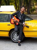 Frontal portrait of cheerful modern multiple race guy in casual clothes near yellow vintage car, play at guitar outside. stock photo