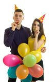 Vertical portrait of cheerful young couple blowing horns on a birthday party Royalty Free Stock Photo