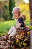 Vertical portrait of cute child girl sitting on the walk with basket of grapes in sunny autumn day Royalty Free Stock Images