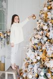 Vertical portrait of female child stands near New Year tree, holds decorated new year ball, decorates fir tree, has happy express royalty free stock photo
