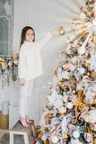Vertical portrait of female child stands near New Year tree, holds decorated new year ball, decorates fir tree, has happy expressi royalty free stock image
