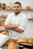 Young man working at his bakery. Vertical portrait of a handsome proud young male baker posing at his store surrounded by freshly baked bread and pastry salesman Stock Photo