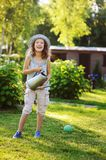 Vertical portrait of happy child girl in gardener hat playing with watering can. In sunny summer garden Stock Photography