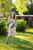 Vertical portrait of happy child girl in gardener hat playing with watering can. In sunny summer garden Royalty Free Stock Photos