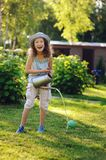 Vertical portrait of happy child girl in gardener hat playing with watering can. In sunny summer garden Royalty Free Stock Photography