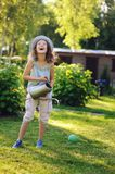 Vertical portrait of happy child girl in gardener hat playing with watering can. In sunny summer garden Stock Images