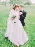 Vertical portrait of the happy newlywed couple standing head-to-head at the background of the green field. royalty free stock images