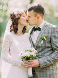 The vertical portrait of the kissing newlyweds with the wedding bouquet in hands. Royalty Free Stock Photos