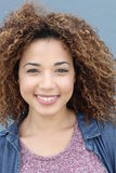 Vertical portrait of latin girl with blond afro hair style smiling portrait on a blue background Royalty Free Stock Photography