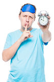 Vertical portrait of a man with an alarm clock shows a gesture Stock Photography